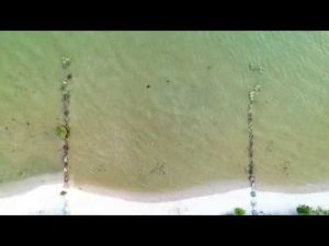 Video clip of a drone flying over water.